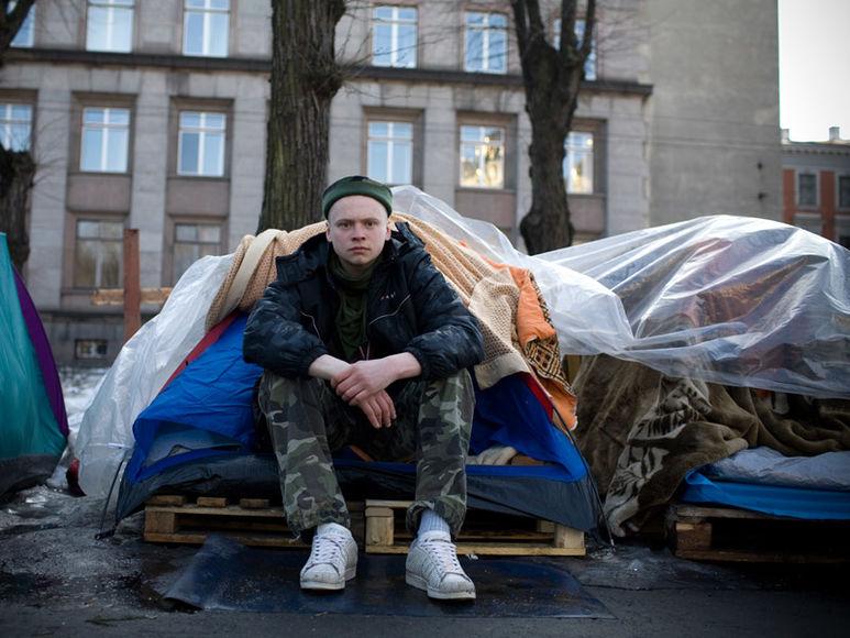 Junger Mann vor seinem Schlafplatz