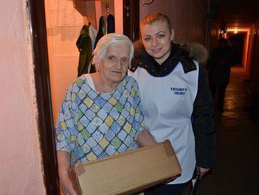 Betreuerin und ältere Frau mit ihrem Paket
