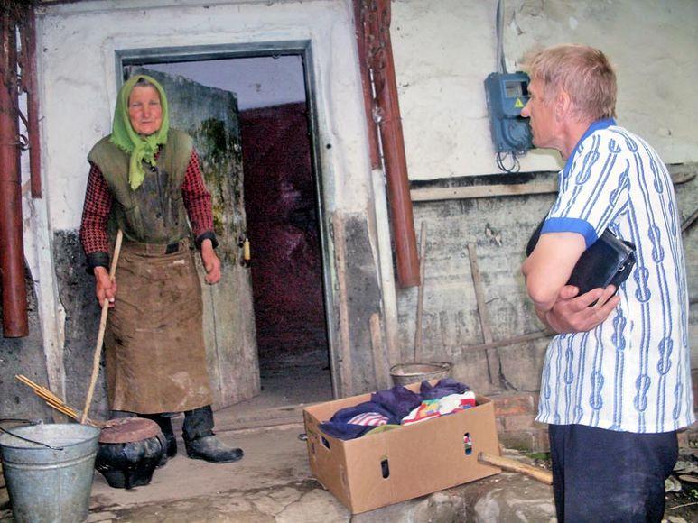 Alte Frau bekommt ein Kleiderpaket