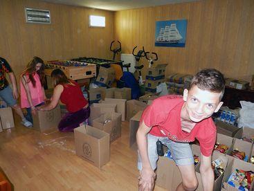 Kinder beim zusammenstellen der Lebensmittelpackete