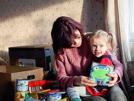 Mutter und Kind beim Auspacken des Kartons