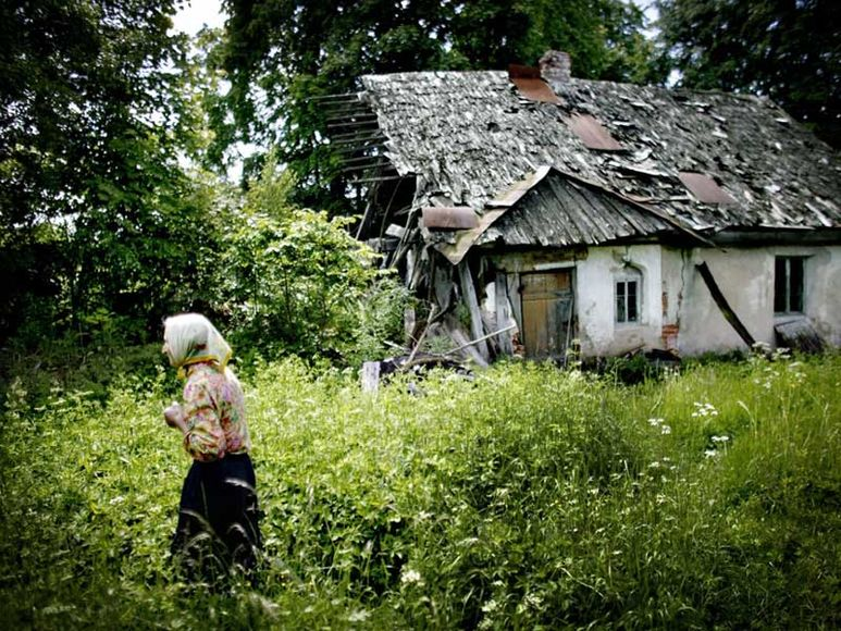 Ältere Frau im Hintergrund ein Haus das zerfällt