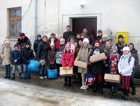 Bewohner eines Dörfchens mit Lebensmittel- und Weihnachtspaketen
