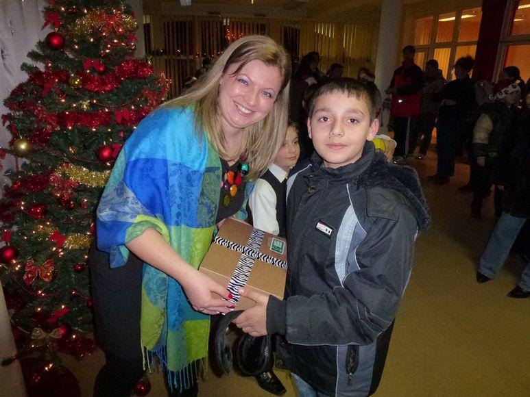 Direktorin Daniela übergibt ein Weihnachtsgeschenk einem Buben