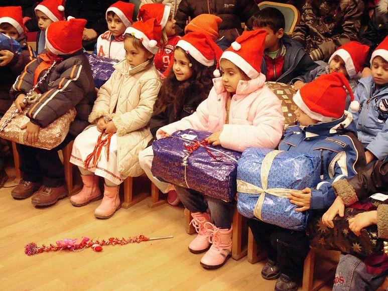 Kinder mit ihren Weihnachtsgeschenken hören gespannt zu