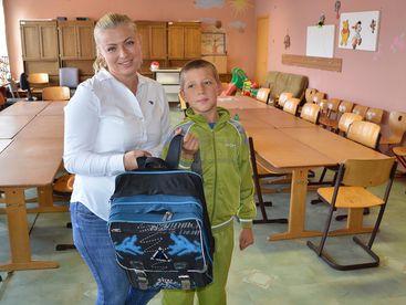 Betreuerin mit Kind und neuem Schulsack