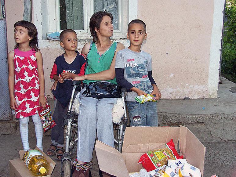Mutter und Kinder erhalten ein Hilfsgüterpaket