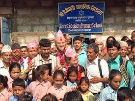 Kinder und Bewohner vor der neuen Schule in Devigath.