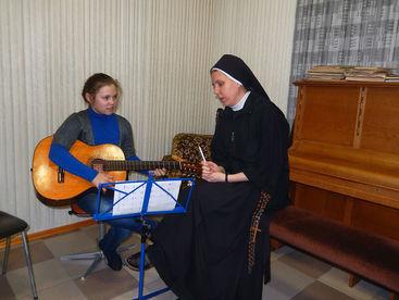Schwester unterrichtet Kind im Gitarrespielen