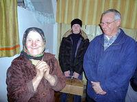 Alte Frau freut sich über Besuch und Hilfsgüter