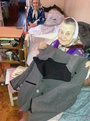 Alte Frau mit Kleidern die sie erhalten hat