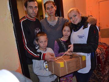 Betreuerin bei der Übergabe eines Paketes an eine Familie