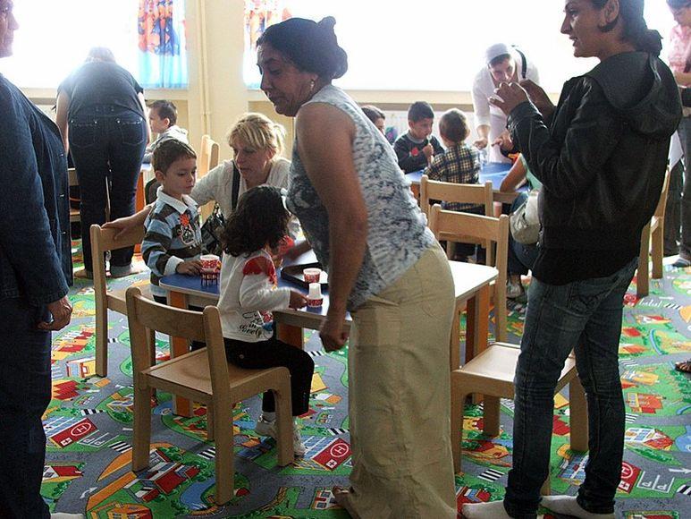Betreuer und Eltern mit ihren Kindern in neuem Klassenzimmer