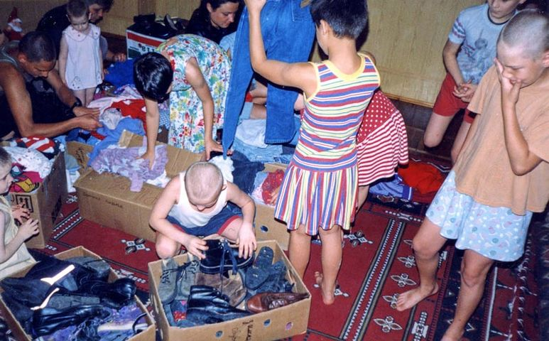 Kinder beim Auspacken von Care-Paketen
