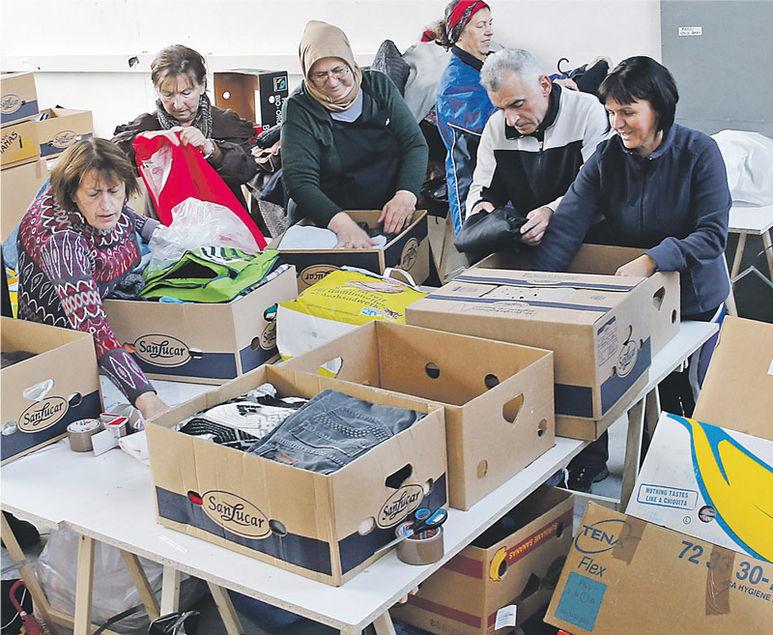 Helfer beim Sortieren der Kleider in Kartons