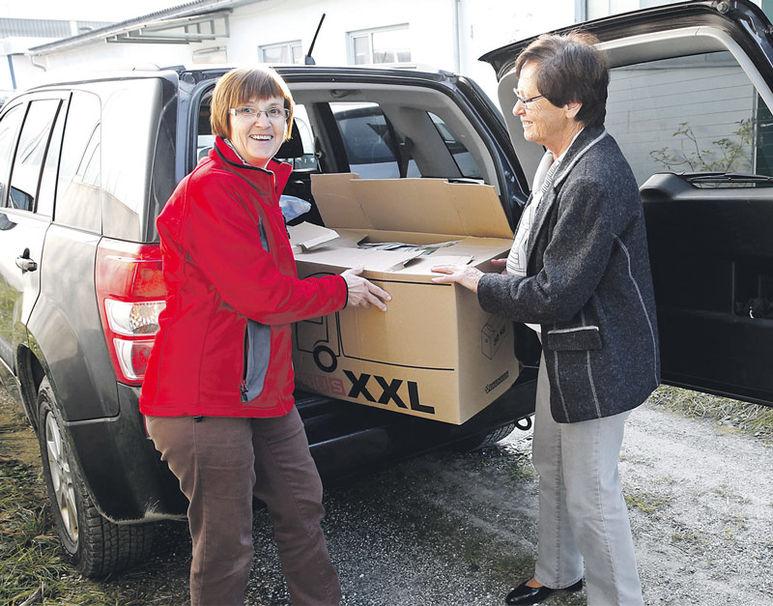 Zwei Frauen beim Ausladen eines Kartons