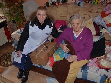 Betreuerin übergibt einer älteren Frau ein Paket