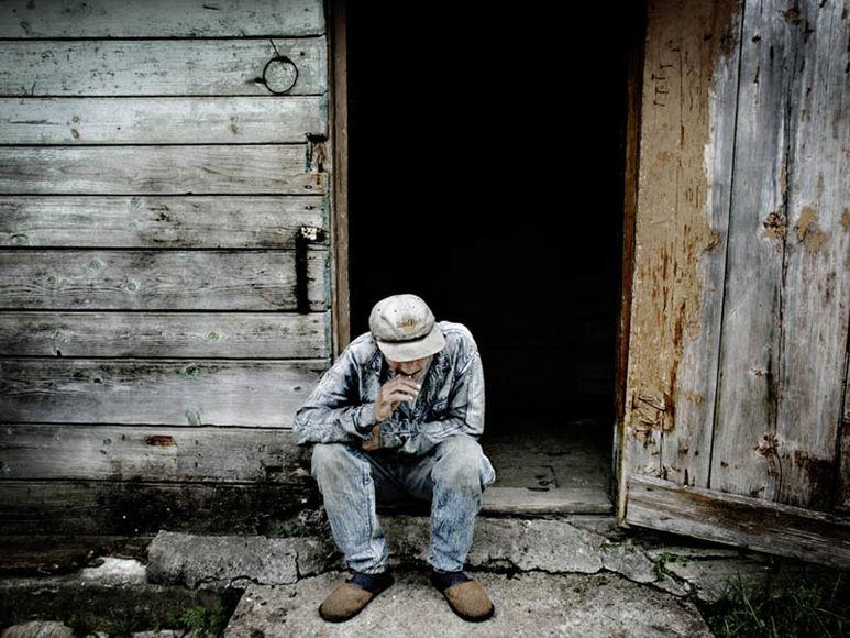 Alter Mann im Eingang eines alten Hauses sitzend