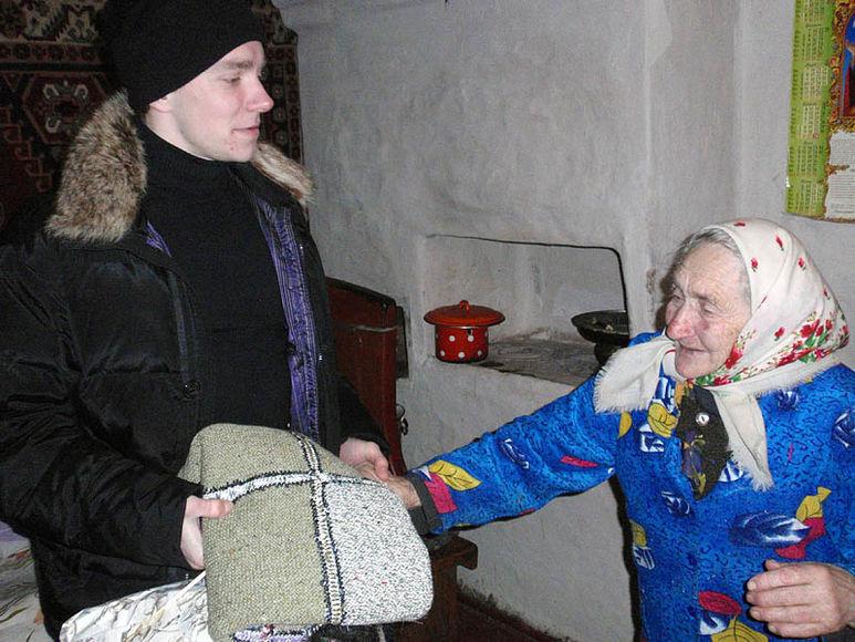 Übergabe einer Decke an eine ältere Frau