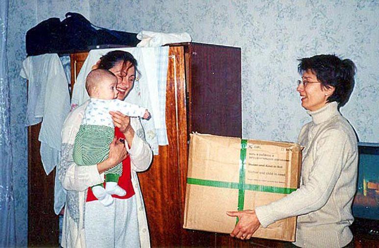 Übergabe eines Care-Paketes an eine Mutter mit Kind