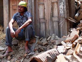 Bewohner sitzt auf Trümmerhaufen