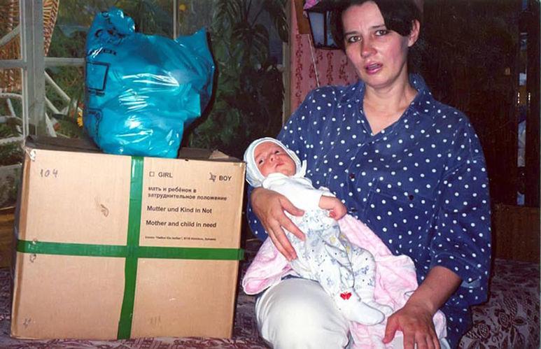 Mutter mit Kind neben Hilfsgüterpaket