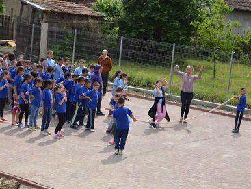Kinder auf dem Sportplatz beim Seilspringen