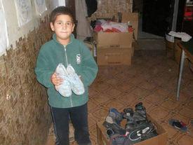 Junger Bub hält neue Schuhe in der Hand