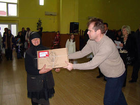 Übergabe eines Care-Paketes an ältere Frau