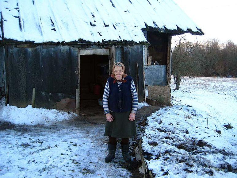 Alte Frau vor ihrem Häuschen