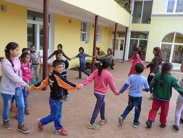 Kinder laufen Hand in Hand im Kreis