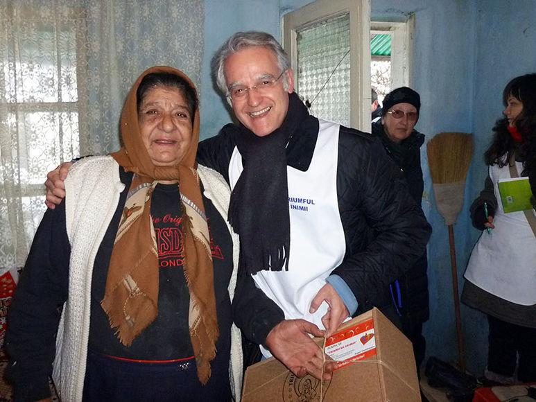 Pater Rolf übergibt ein er älteren Frau ein Hilfspaket