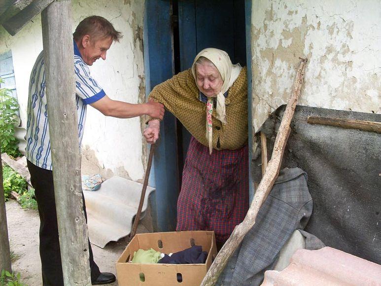 Br. Bruno hilft älterer Frau aus dem Haus