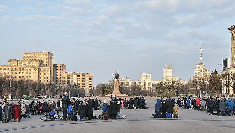 Menschengruppen beim Beten auf dem Platz