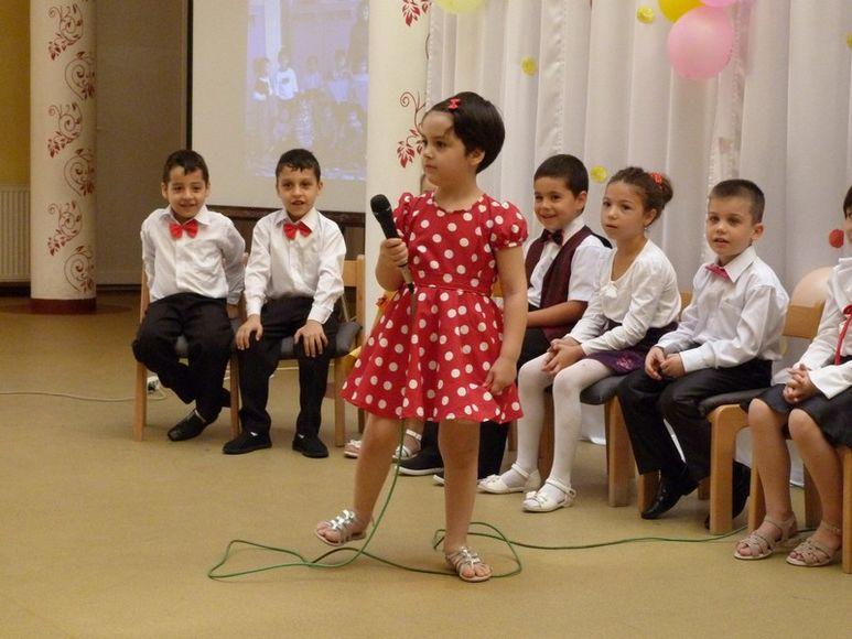 Mädchen mit Mikrophon vor einer Gruppe Kinder