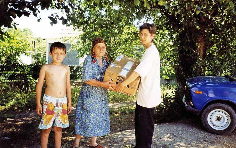 Übergabe eines Hilfsgüterpaket an eine ältere Frau