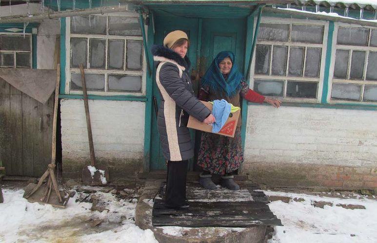 Übergabe eines Hilfspaketes an eine alte Frau
