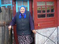 Alte Frau vor ihrem Haus