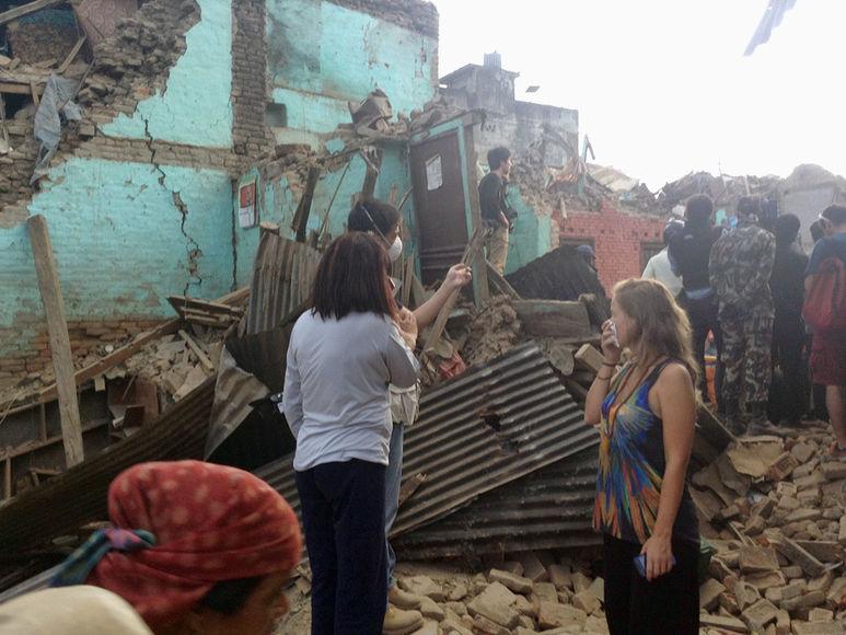 Menschen stehen vor ihren zerstörten Häusern